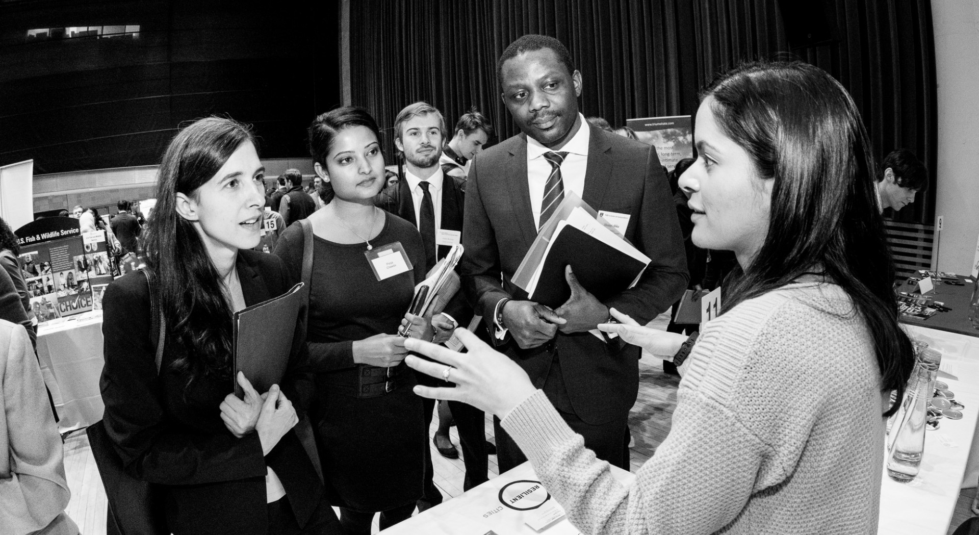 black and white photo of students speaking with a recruiter
